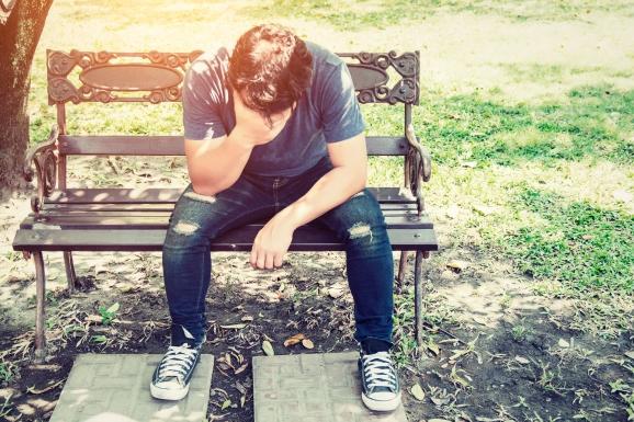 Headache man sitting on bench.